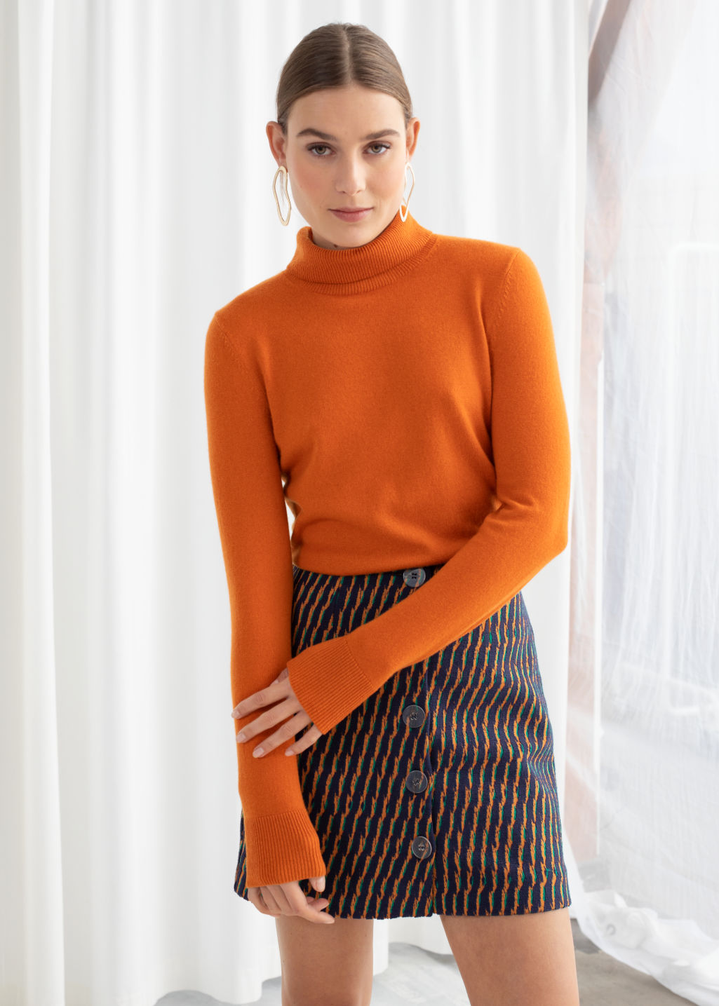Model front image of Stories fitted cashmere turtleneck in orange