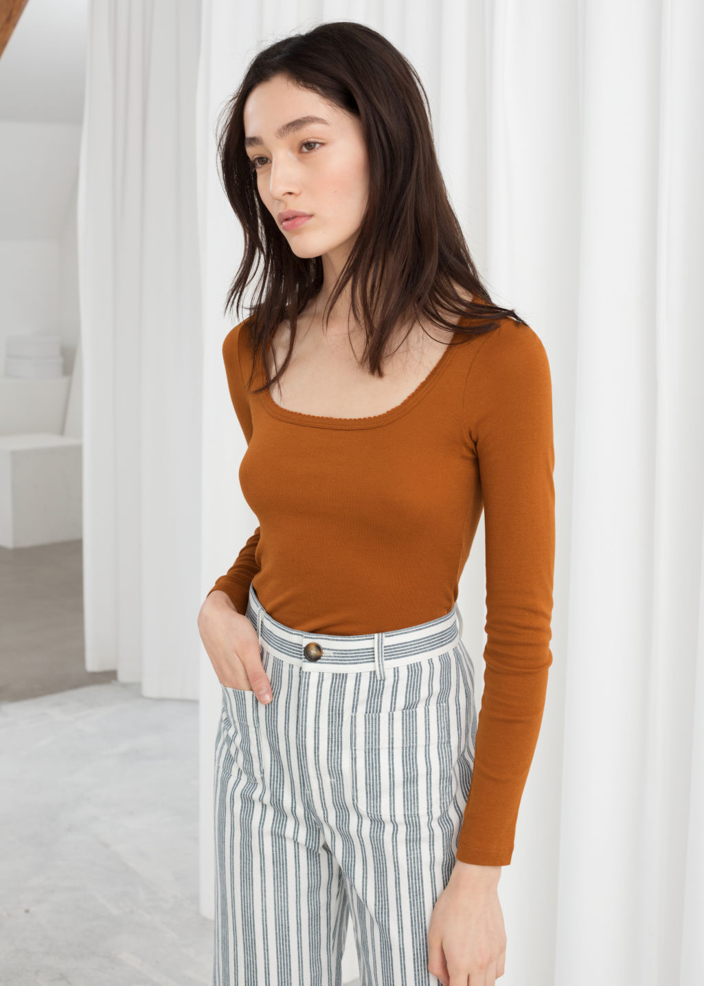 Model front image of Stories organic cotton long sleeve top in orange