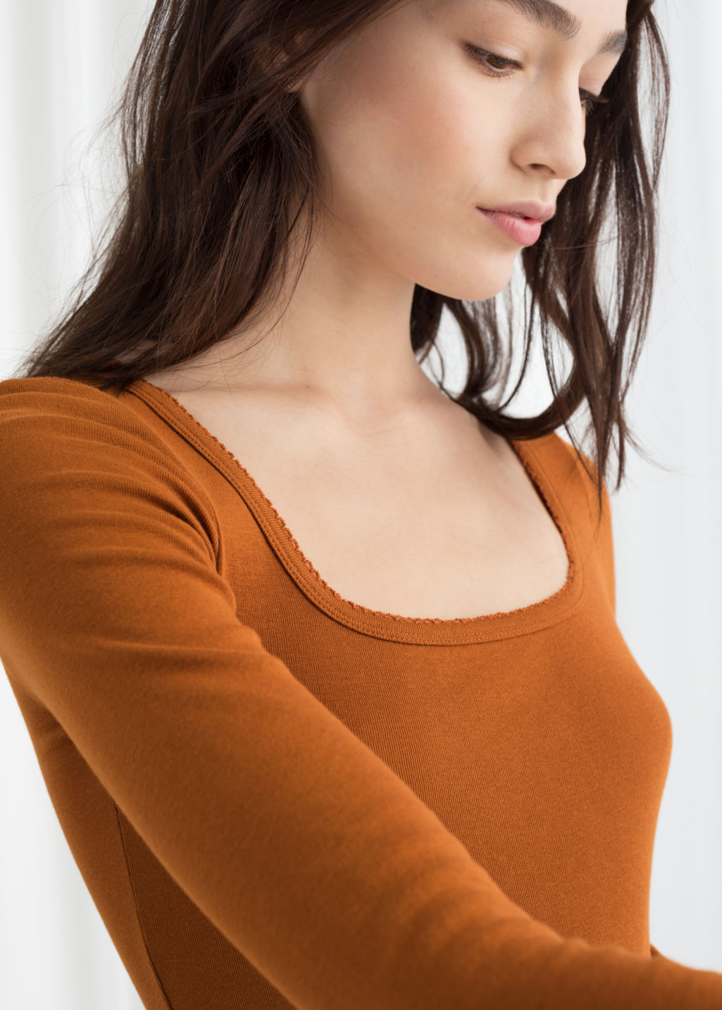Model back image of Stories organic cotton long sleeve top in orange