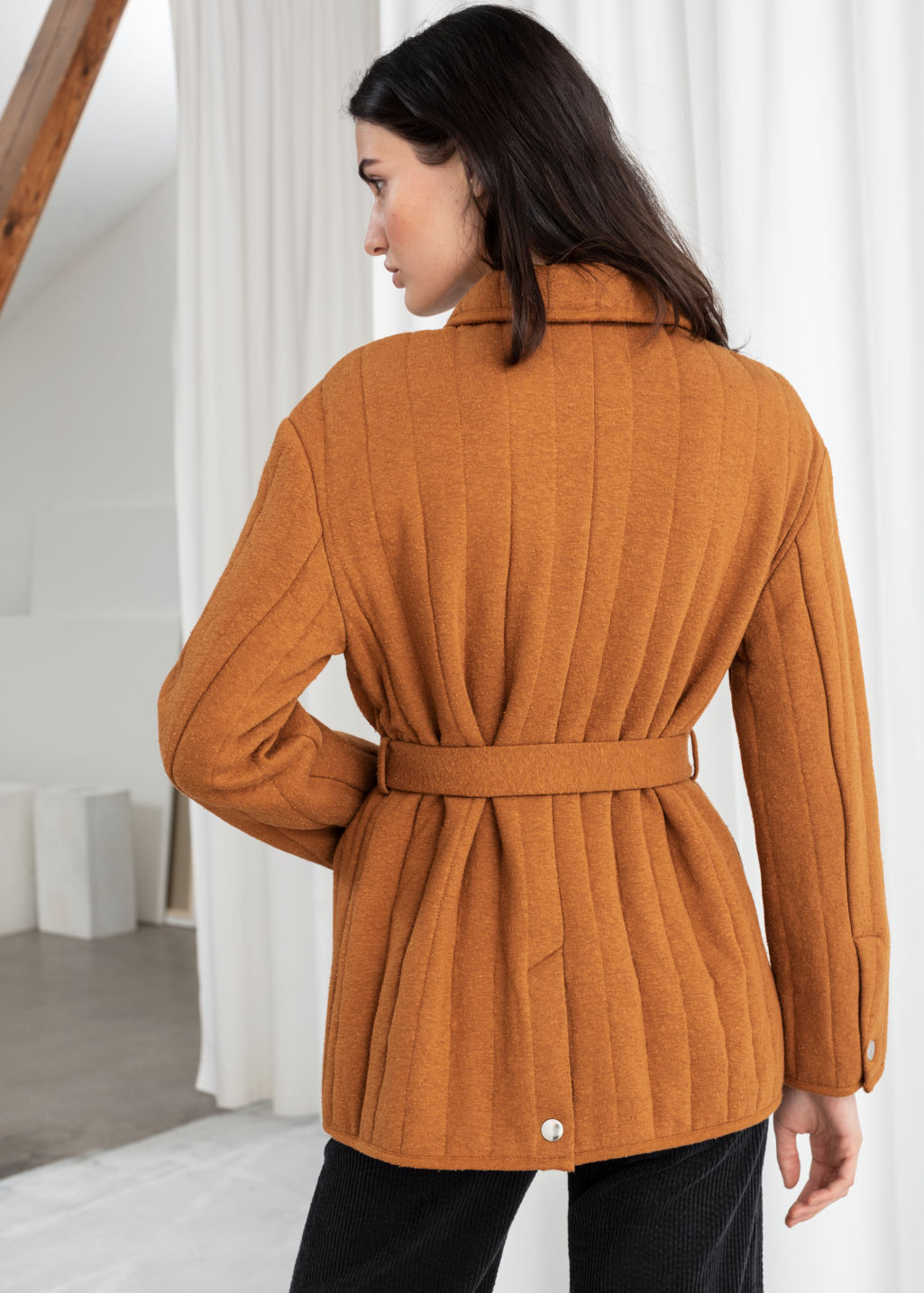Model back image of Stories quilted belted jacket in orange