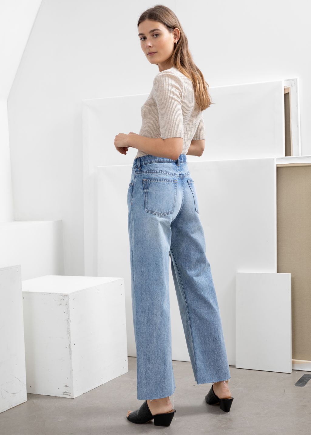 Model back image of Stories kick flare mid rise jeans in blue