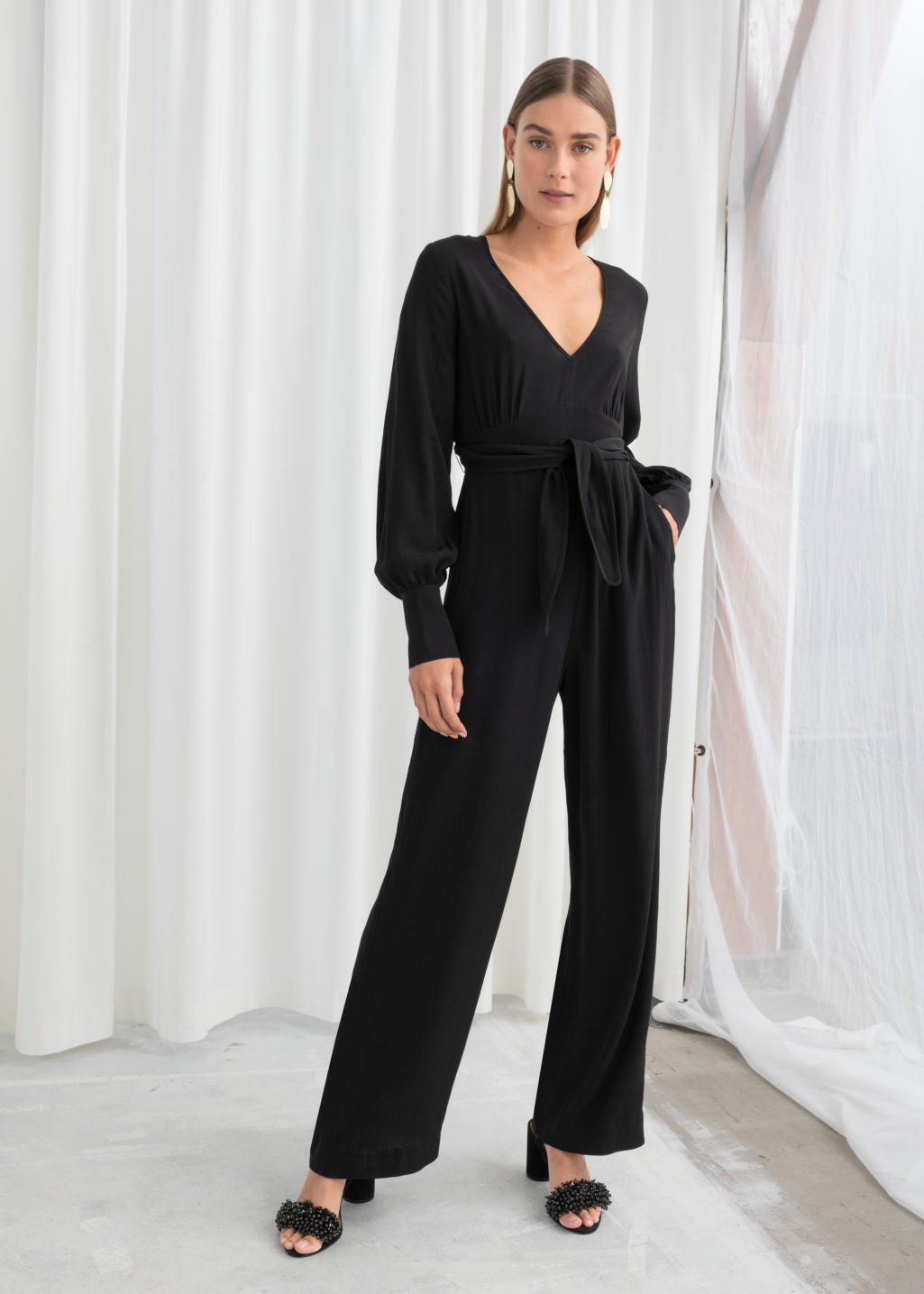 Model front image of Stories plunging belted jumpsuit  in black
