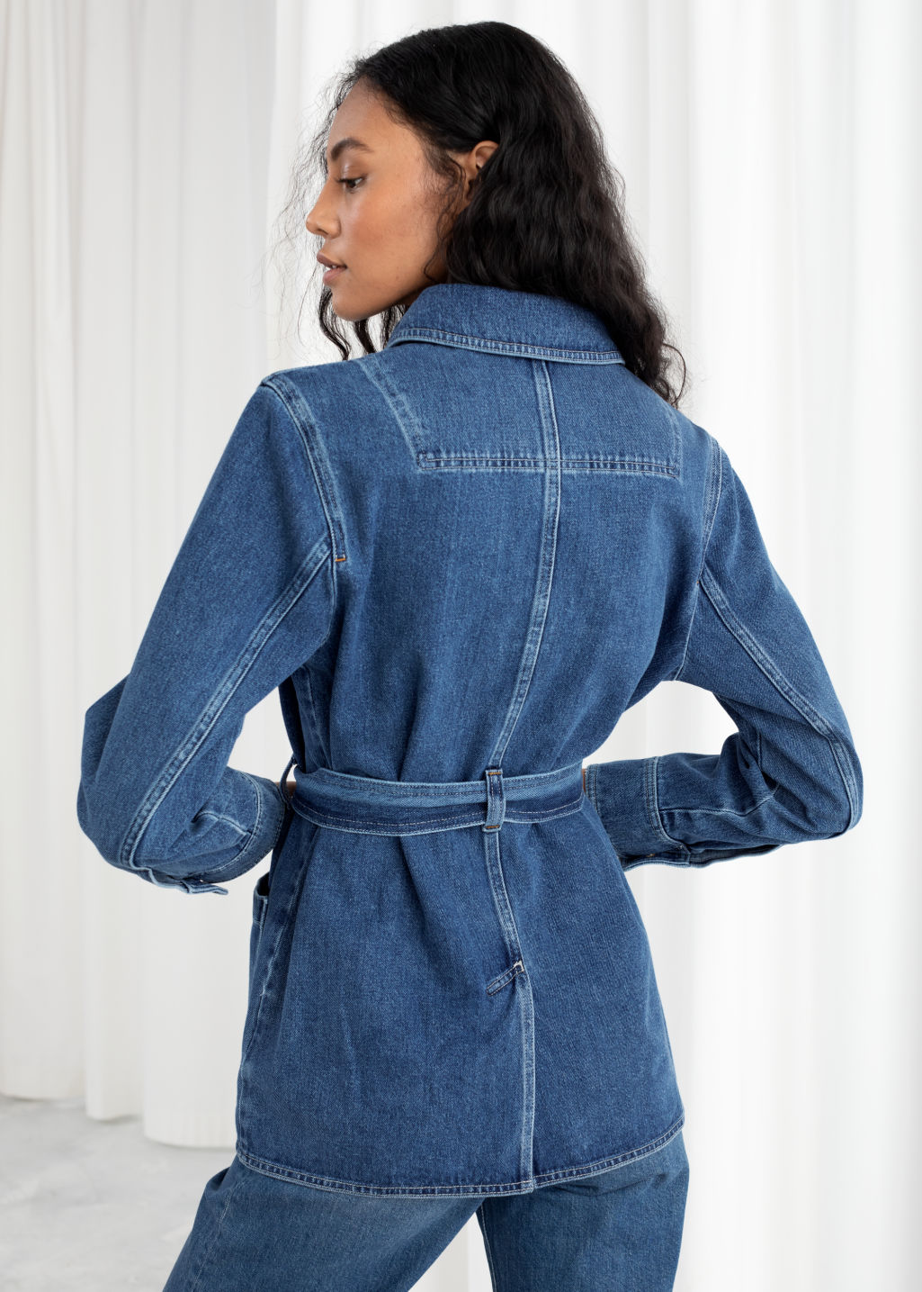 Model back image of Stories belted workwear denim jacket in blue