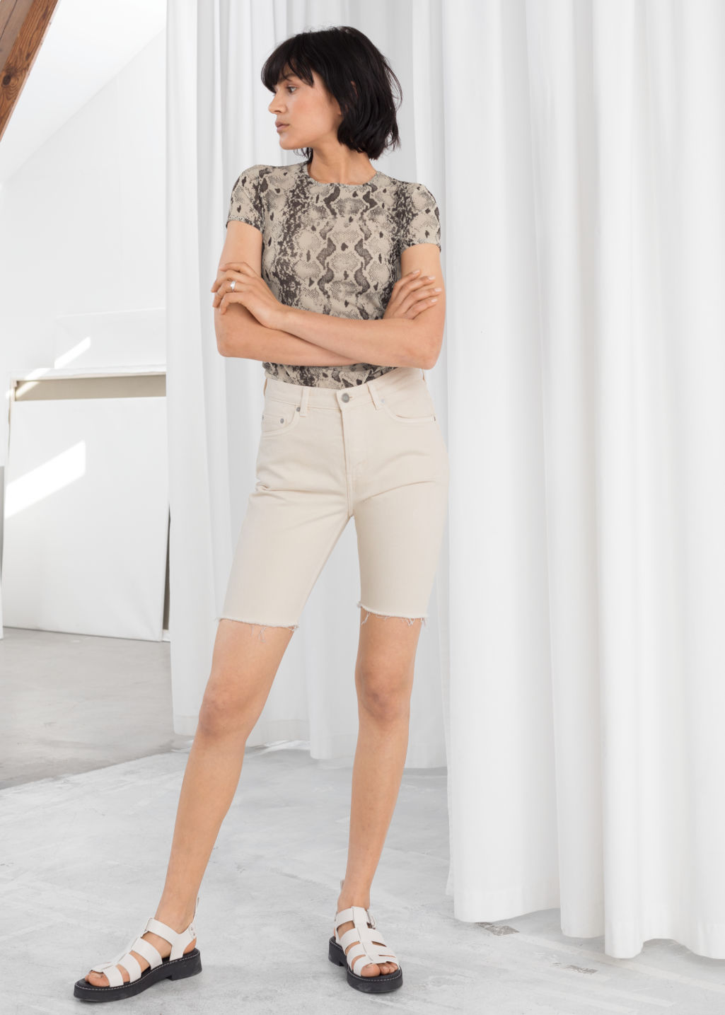 Model front image of Stories raw edge denim bermuda shorts in white