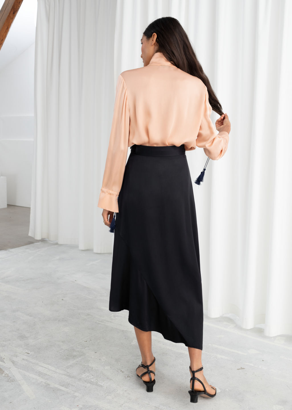 Model back image of Stories asymmetric satin midi skirt in black