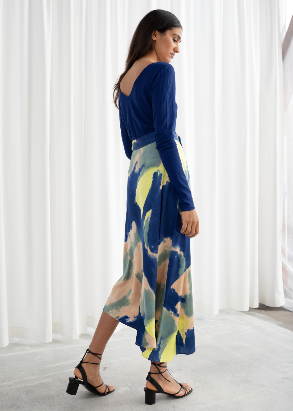 Model back image of Stories asymmetric satin midi skirt in blue