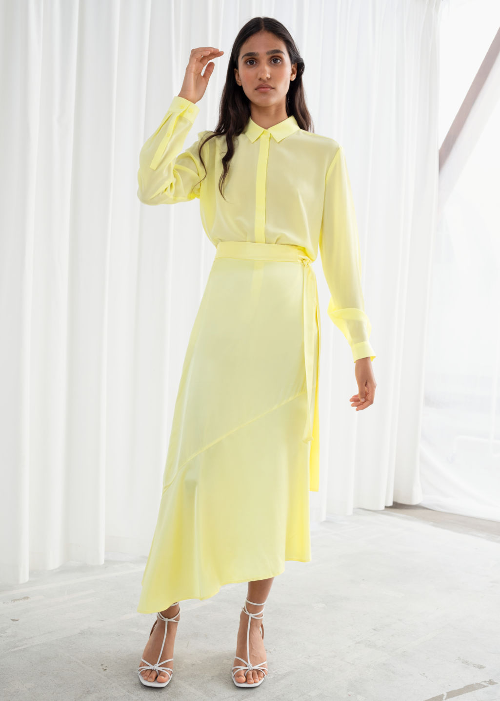 Model front image of Stories asymmetric satin midi skirt in yellow