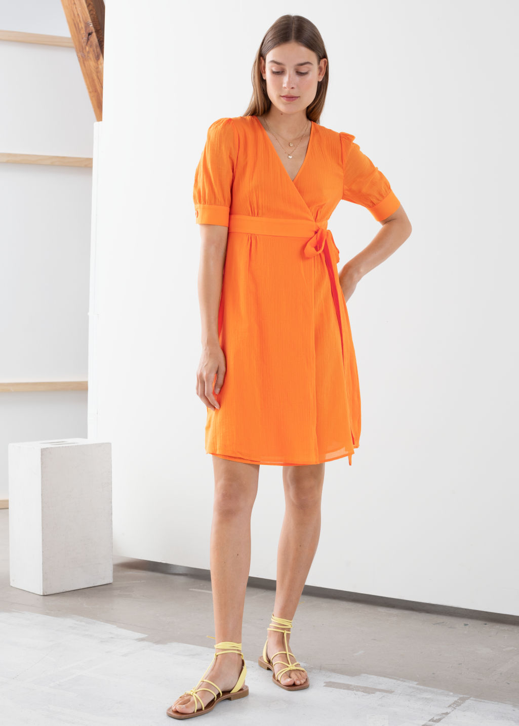 Model front image of Stories cotton blend wrap mini dress in orange