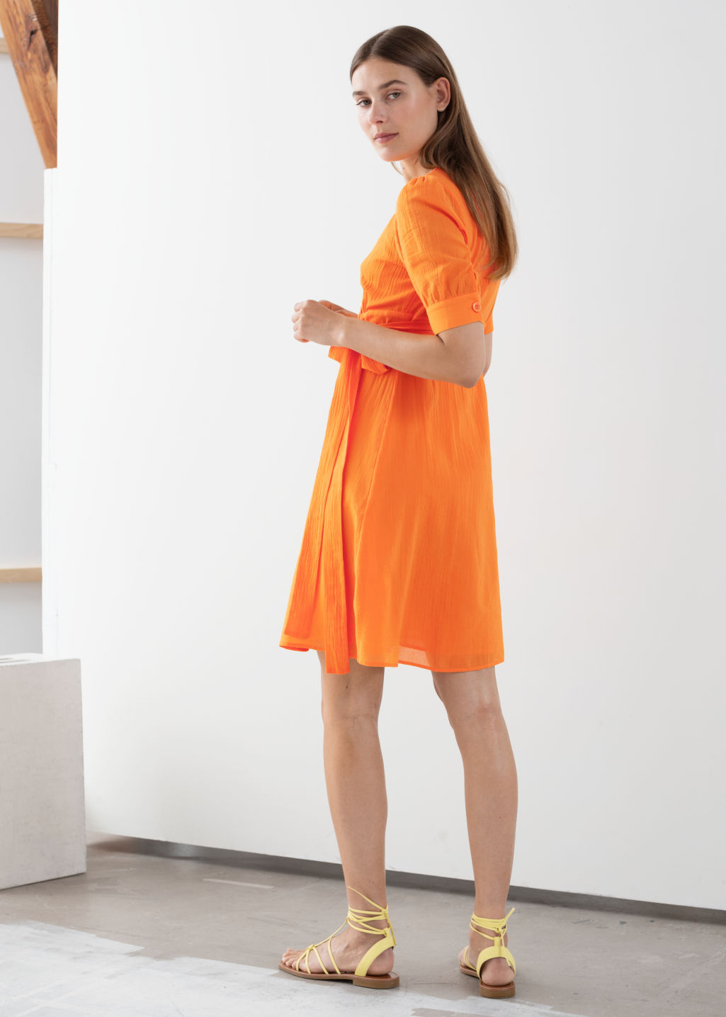 Model back image of Stories cotton blend wrap mini dress in orange