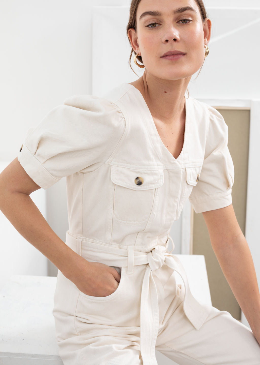 Model front image of Stories belted puff sleeve denim jumpsuit in white