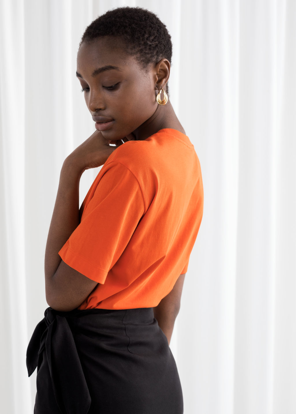 Model back image of Stories organic cotton graphic t-shirt in orange