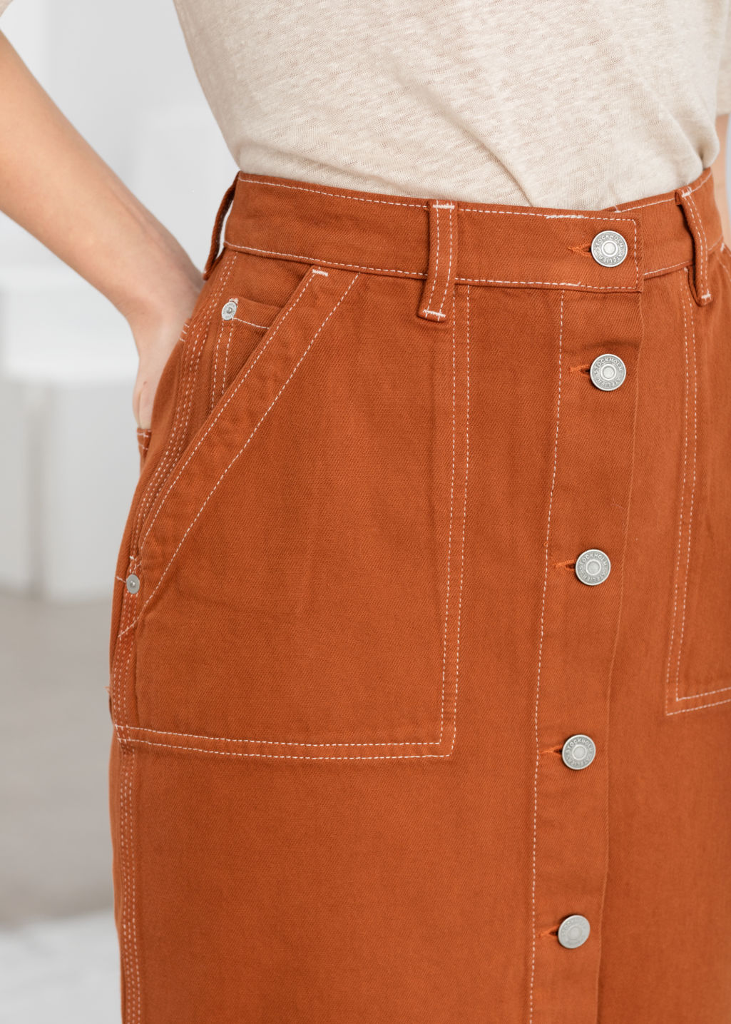 Model back image of Stories mid rise denim midi skirt in orange