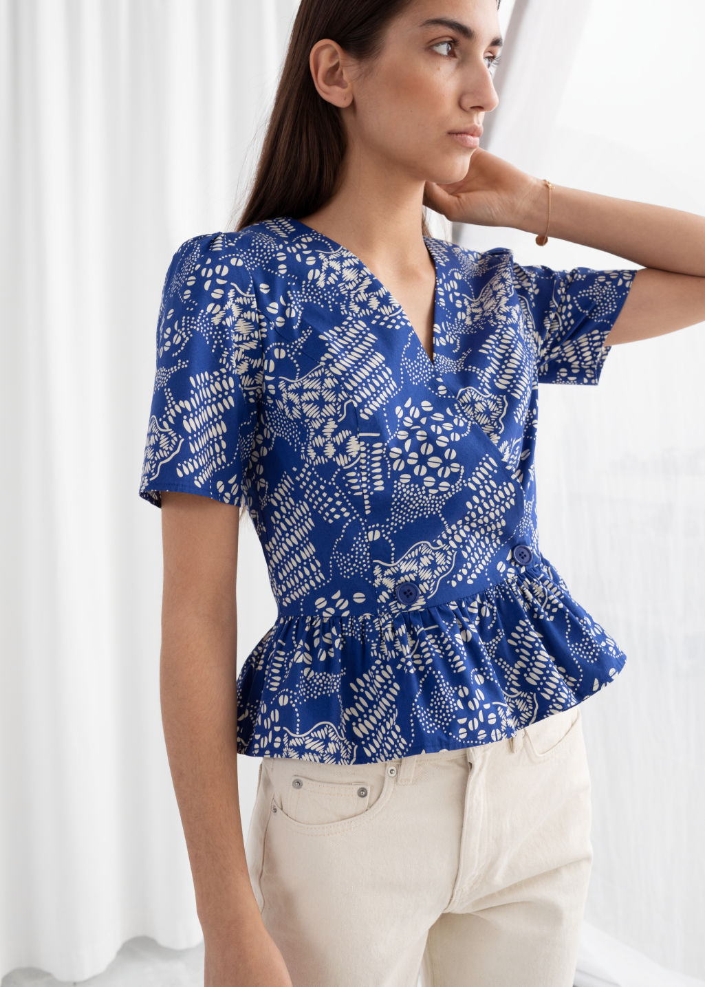 Model front image of Stories cotton coffee bean wrap blouse in blue