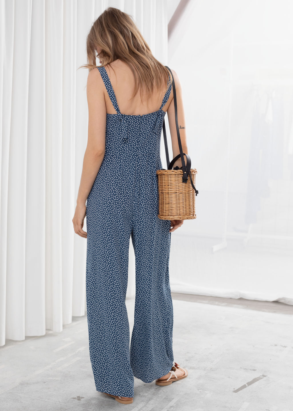 Model back image of Stories relaxed floral jumpsuit in blue