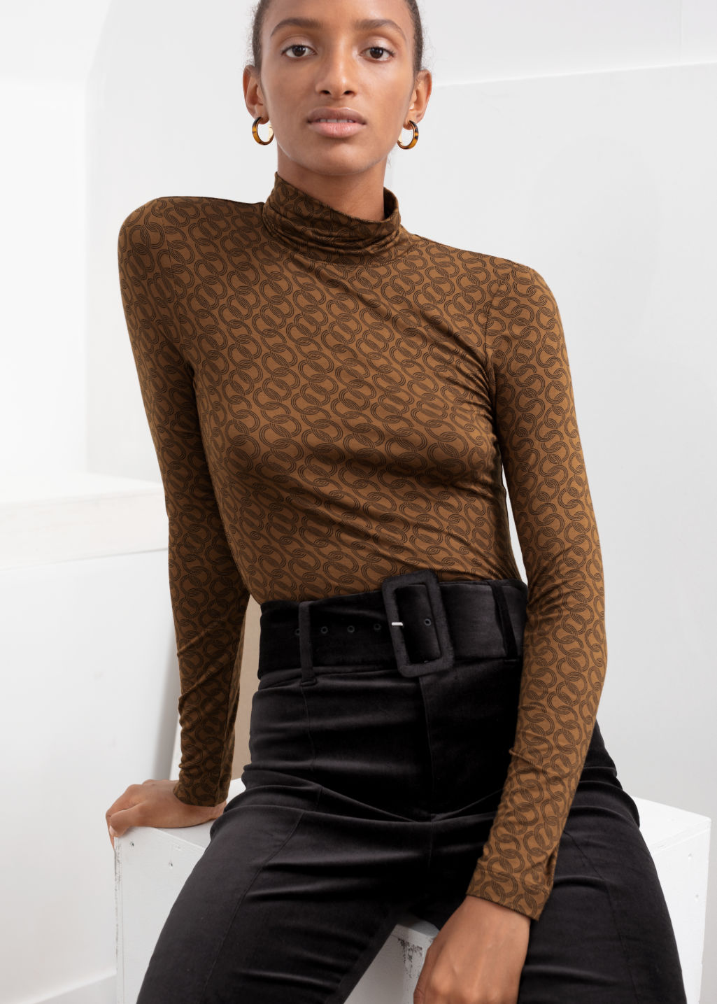Model front image of Stories fitted stretch turtleneck top in beige