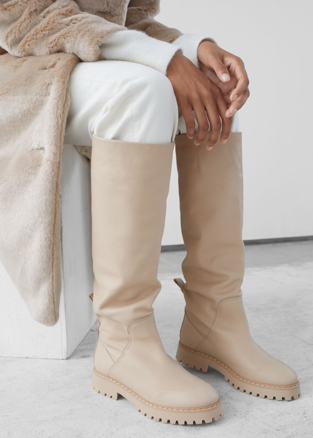 Model side image of Stories topstitched knee high leather boots in white
