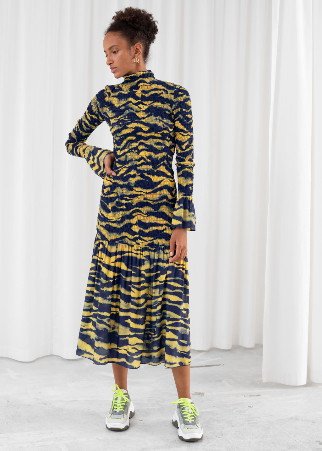 Model front image of Stories tiger smocked midi ruffle dress in yellow