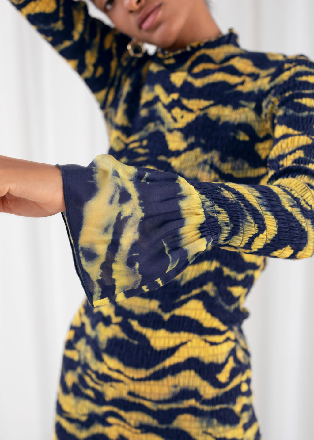 Model back image of Stories tiger smocked midi ruffle dress in yellow