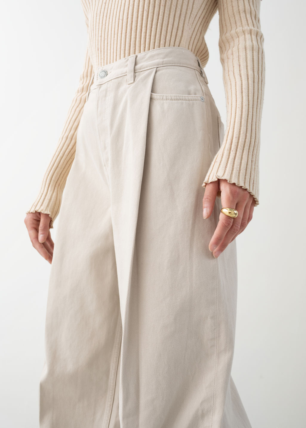 Model back image of Stories relaxed high rise pleat jeans in beige