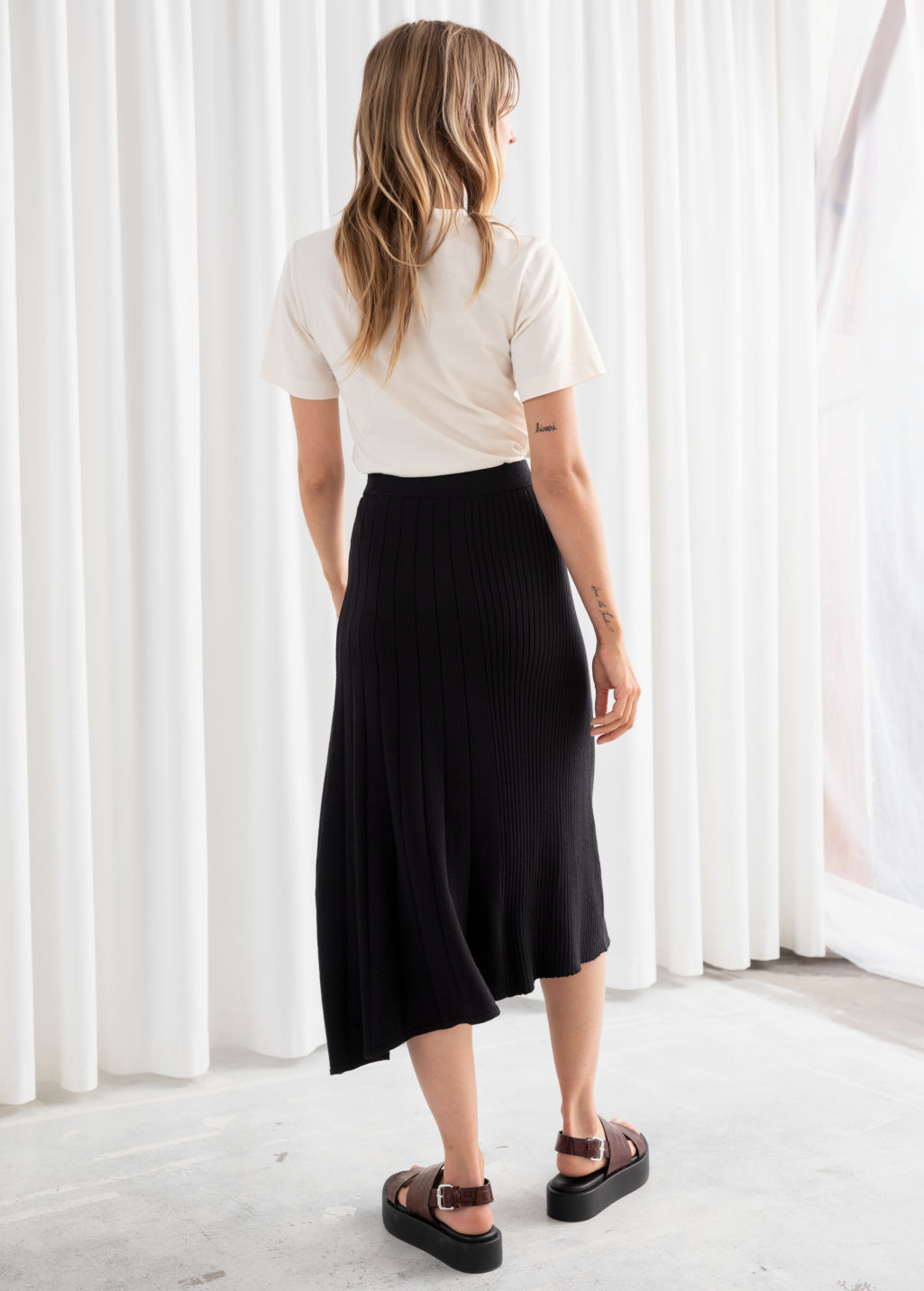 Model back image of Stories asymmetrical pleated knit midi skirt in black