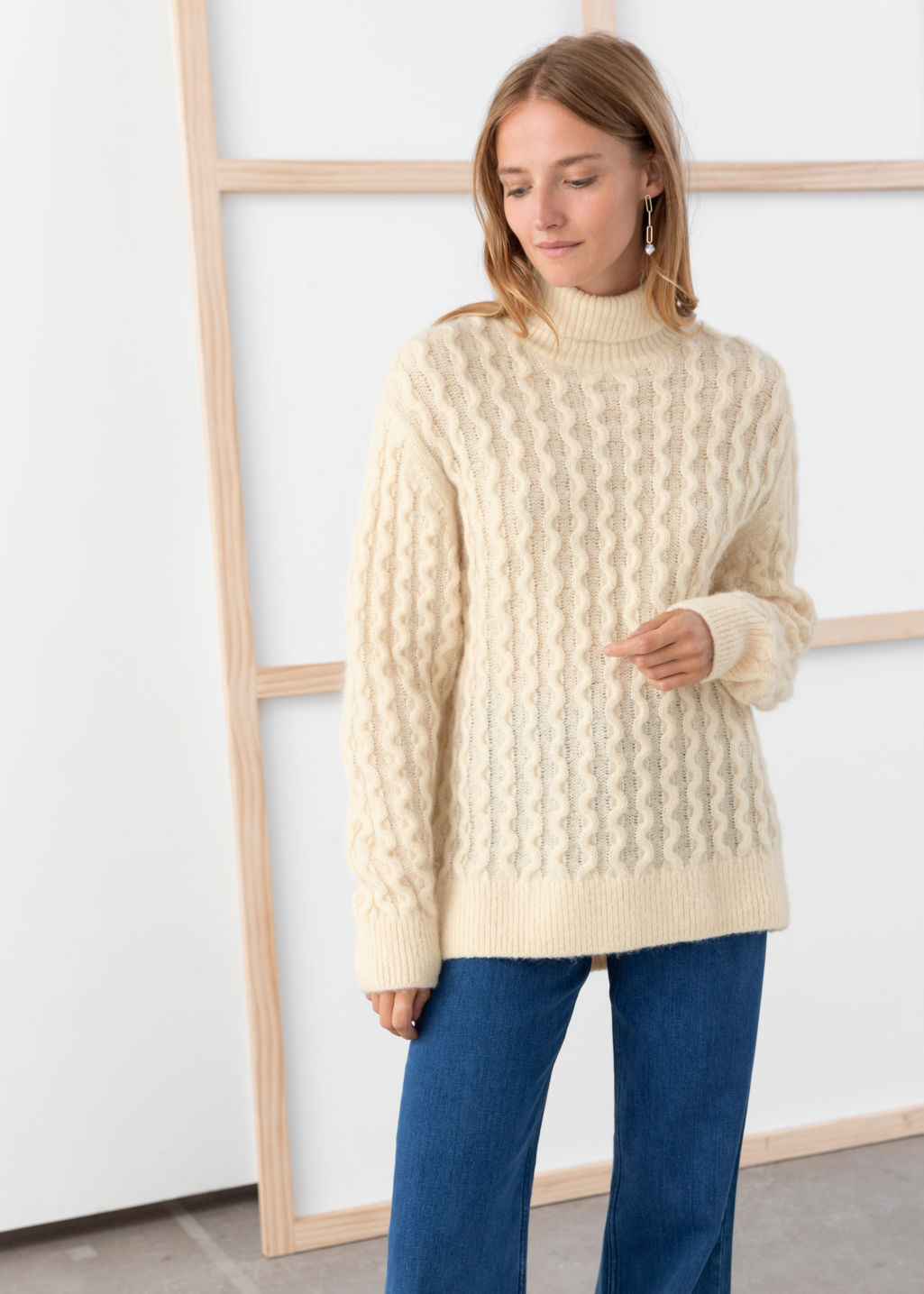 Model front image of Stories cable knit turtleneck sweater in beige