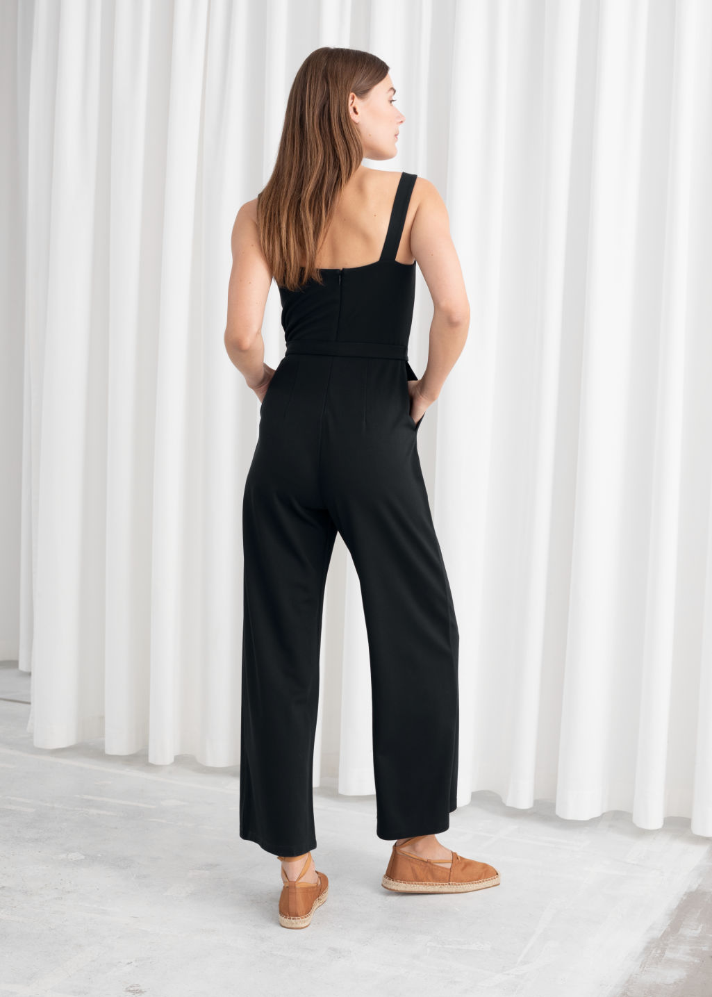 Model back image of Stories belted square neck jumpsuit in black