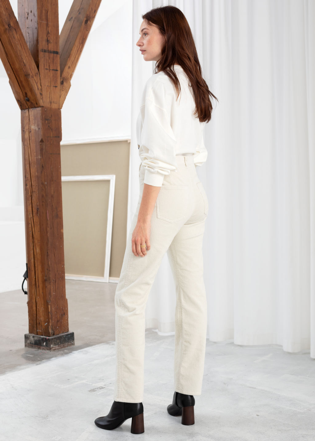 Model back image of Stories high rise tapered corduroy trousers in white