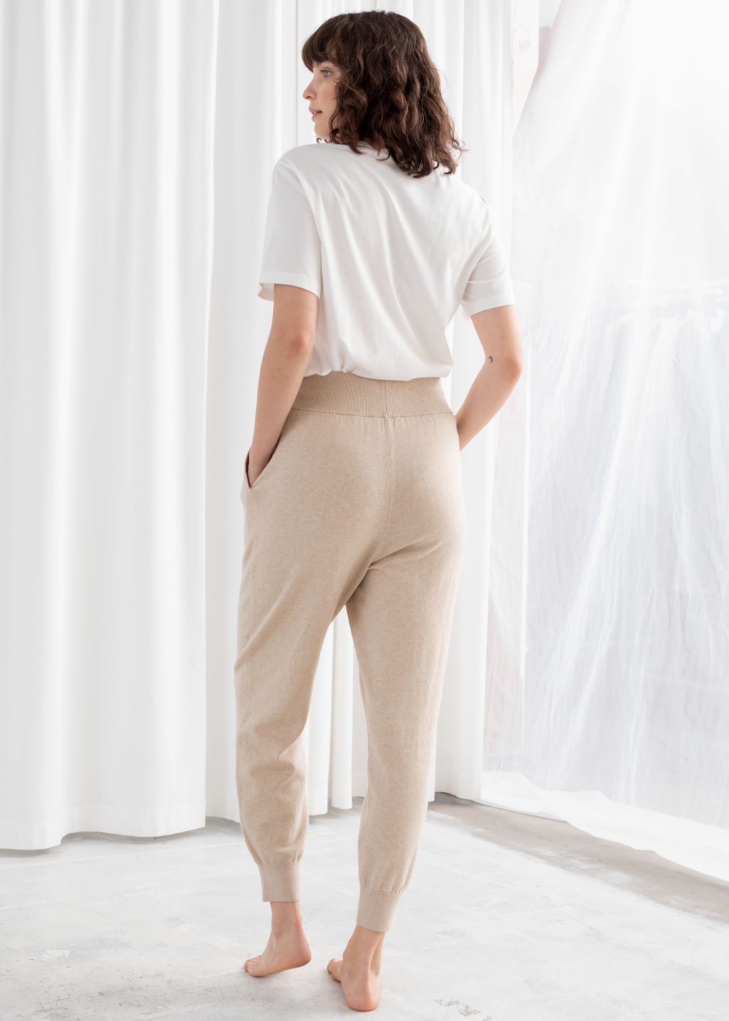 Model back image of Stories cashmere blend jogger trousers in beige
