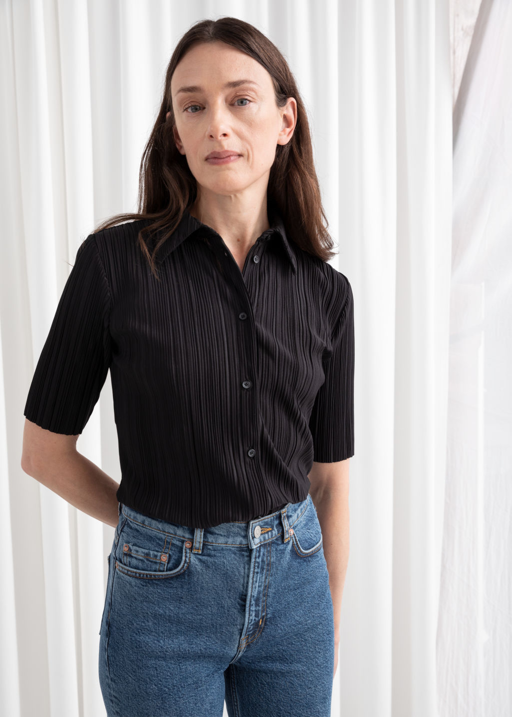 Model front image of Stories plissé pleated button down blouse in black