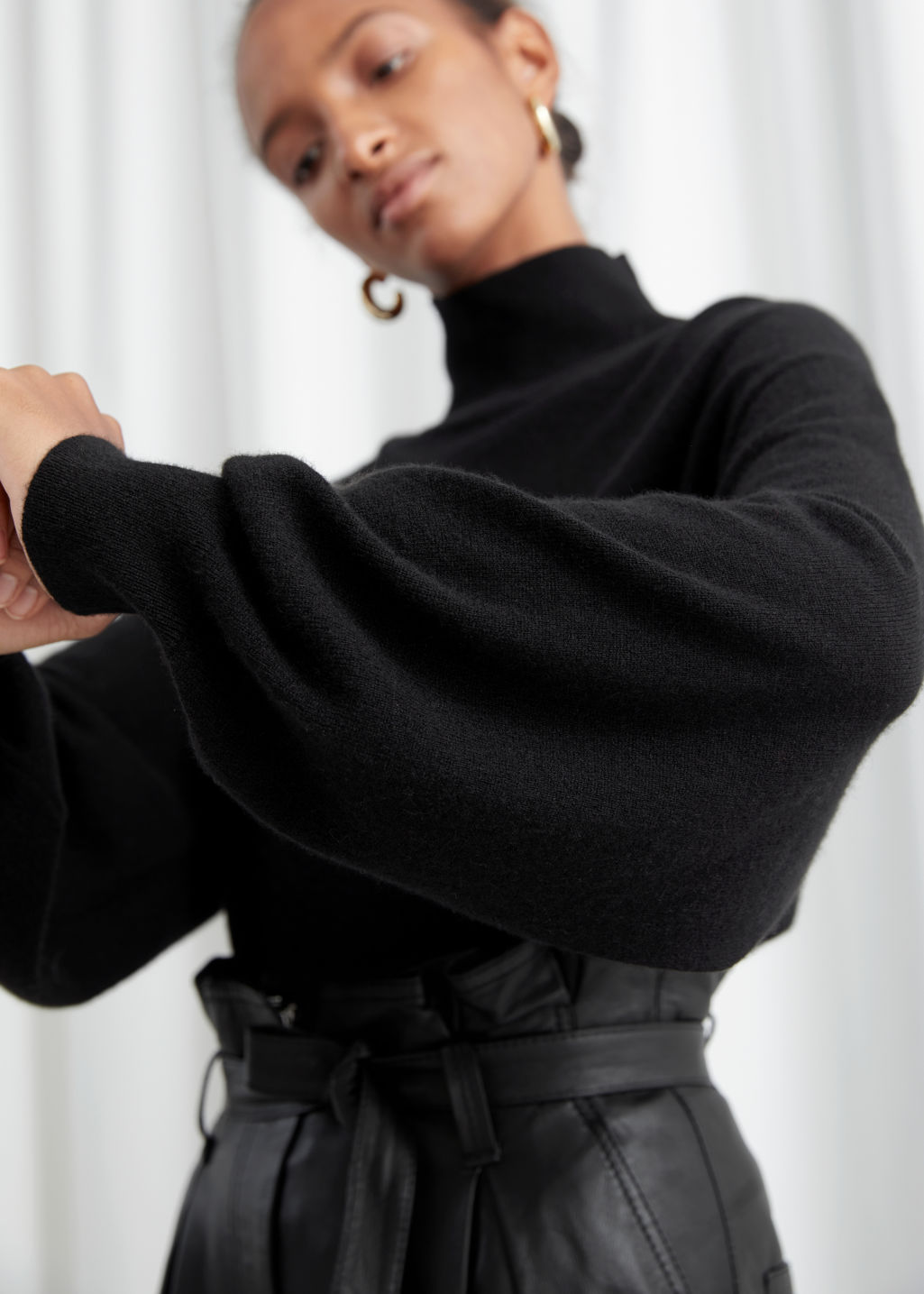 Model side image of Stories cashmere puff sleeve turtleneck in black