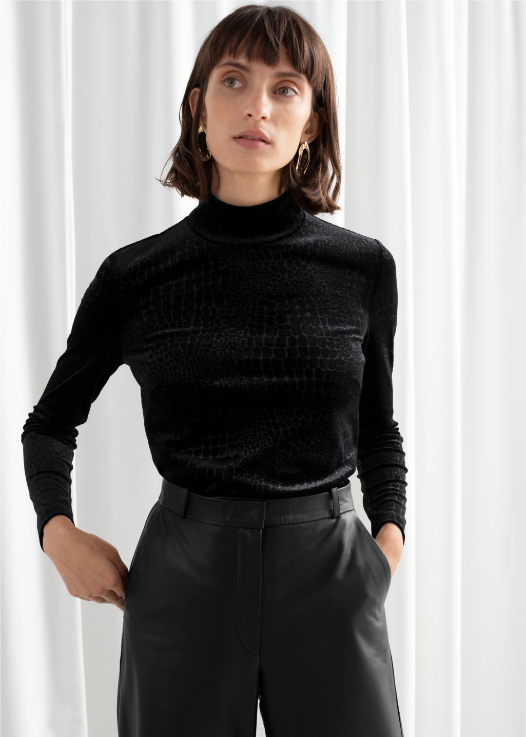 Model front image of Stories croco print velour turtleneck top in black