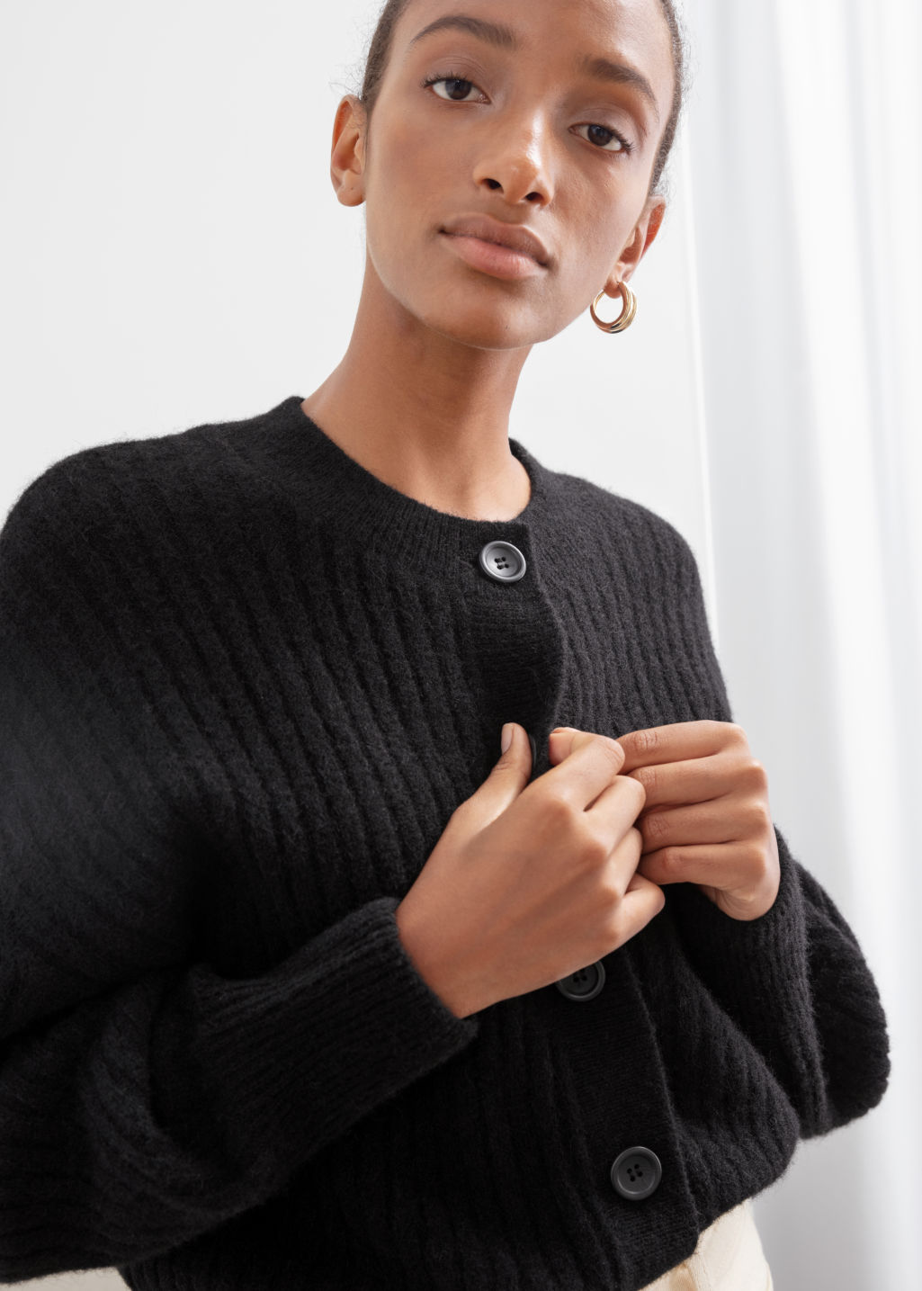 Model front image of Stories oversized ribbed crewneck cardigan in black