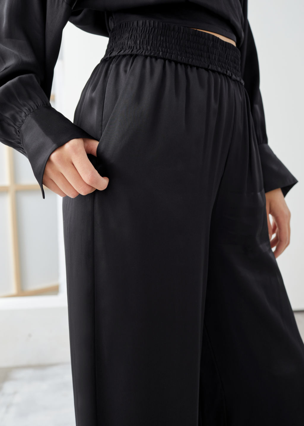 Model side image of Stories satin wide leg flowy trousers in black