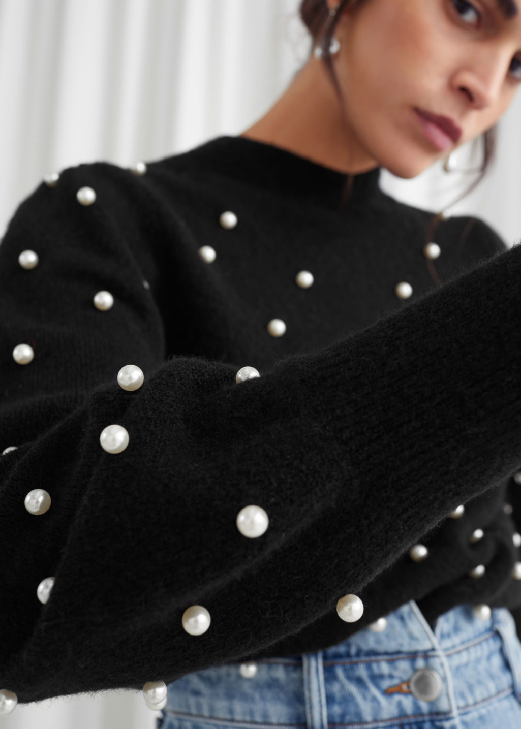 Model side image of Stories pearl dot puff sleeve sweater in black