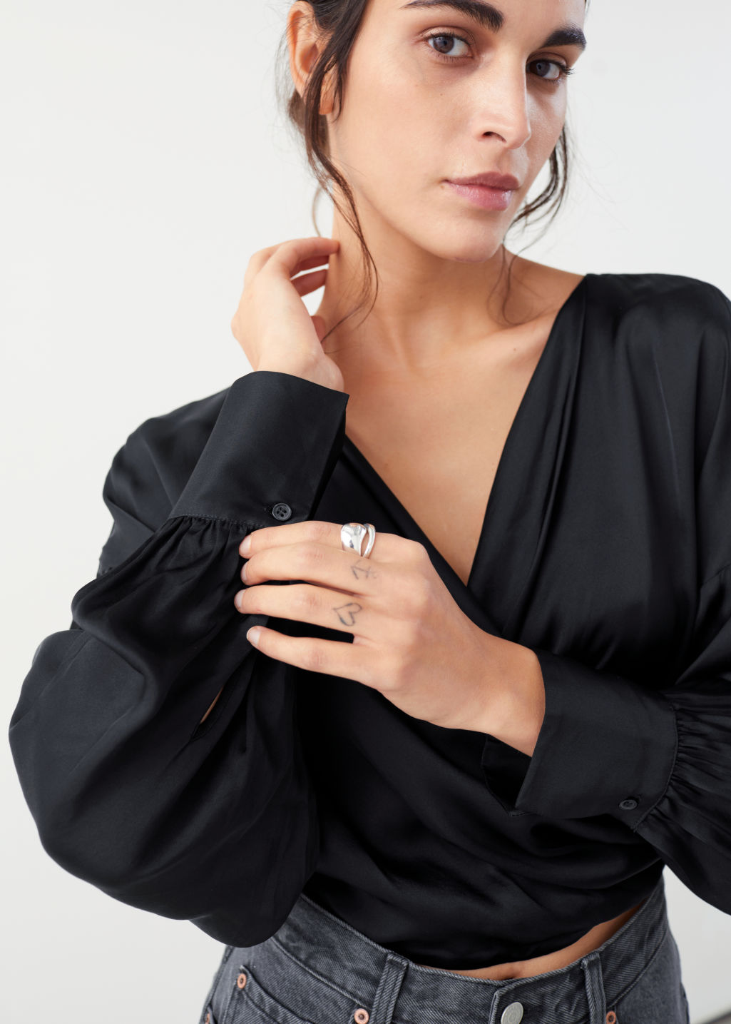 Model front image of Stories draped satin wrap blouse in black