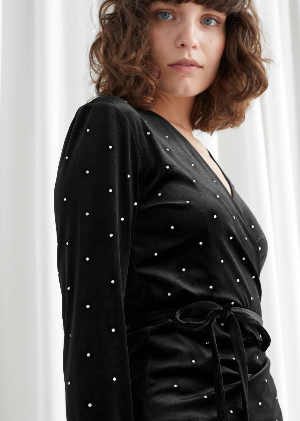 Model side image of Stories rhinestone velvet wrap blouse in black