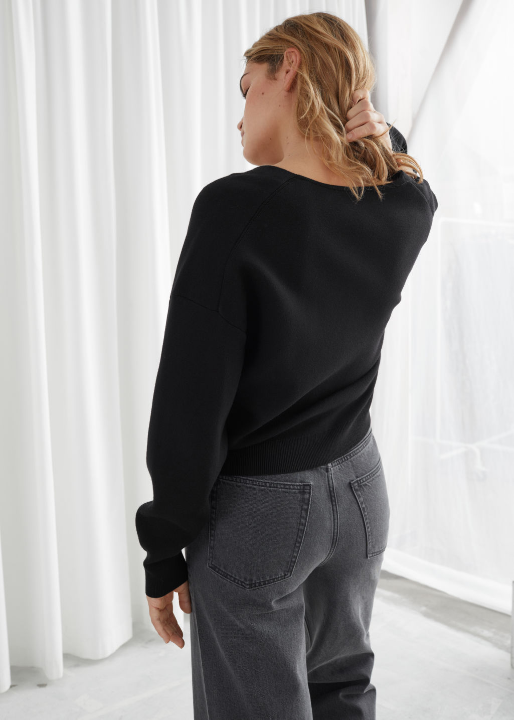 Model back image of Stories boxy plunging v-cut cardigan in black