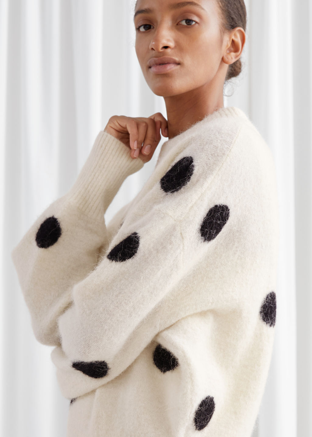 Model side image of Stories wool blend polka dot sweater in white