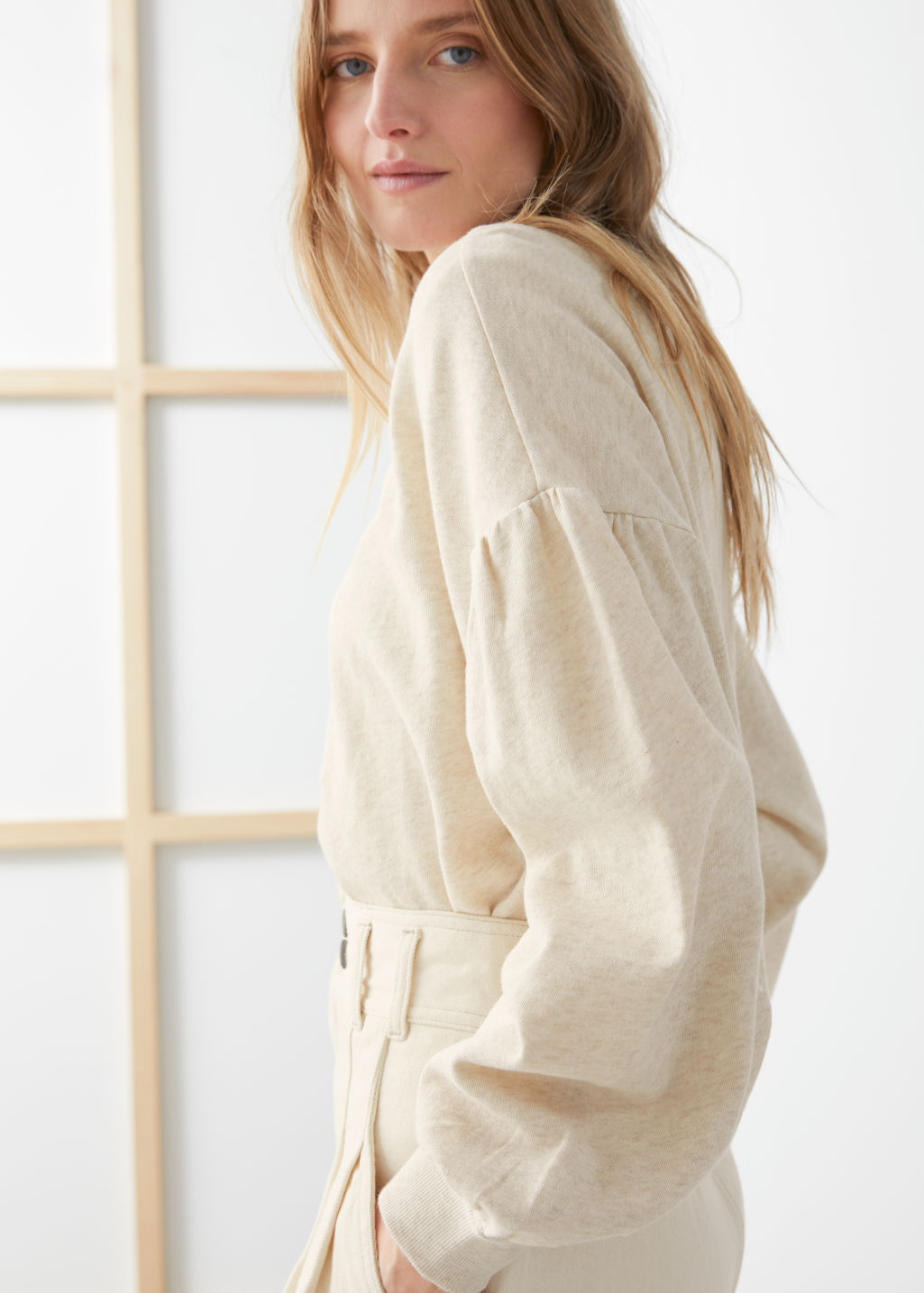 Model side image of Stories organic cotton puff sleeve sweater in beige