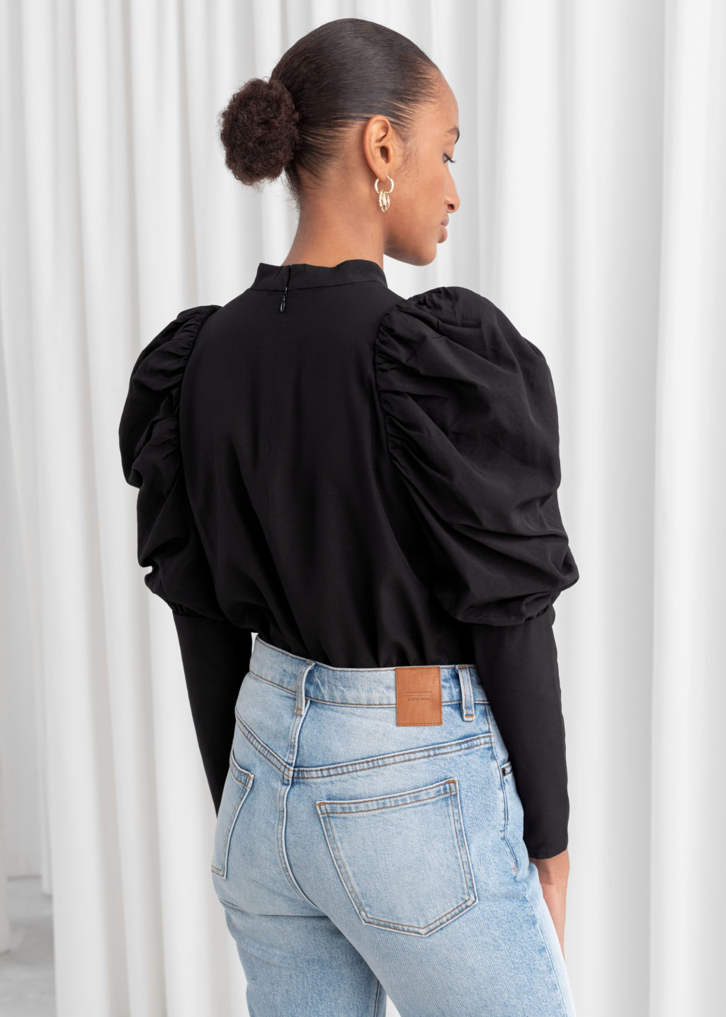 Model back image of Stories puff shoulder mock neck blouse in black