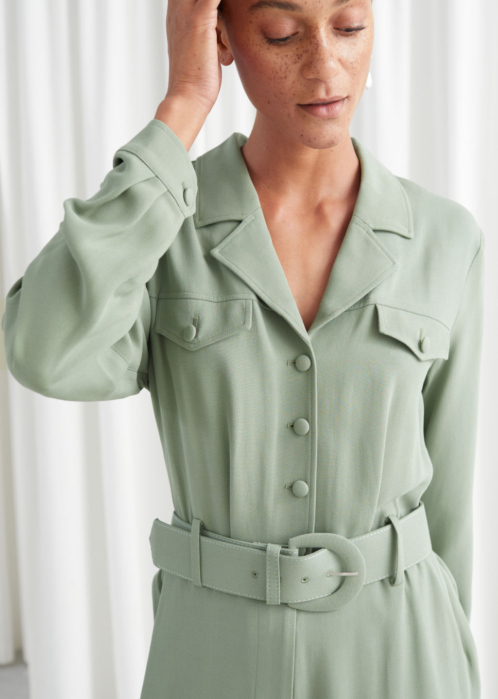 Model front image of Stories belted long sleeve jumpsuit in green