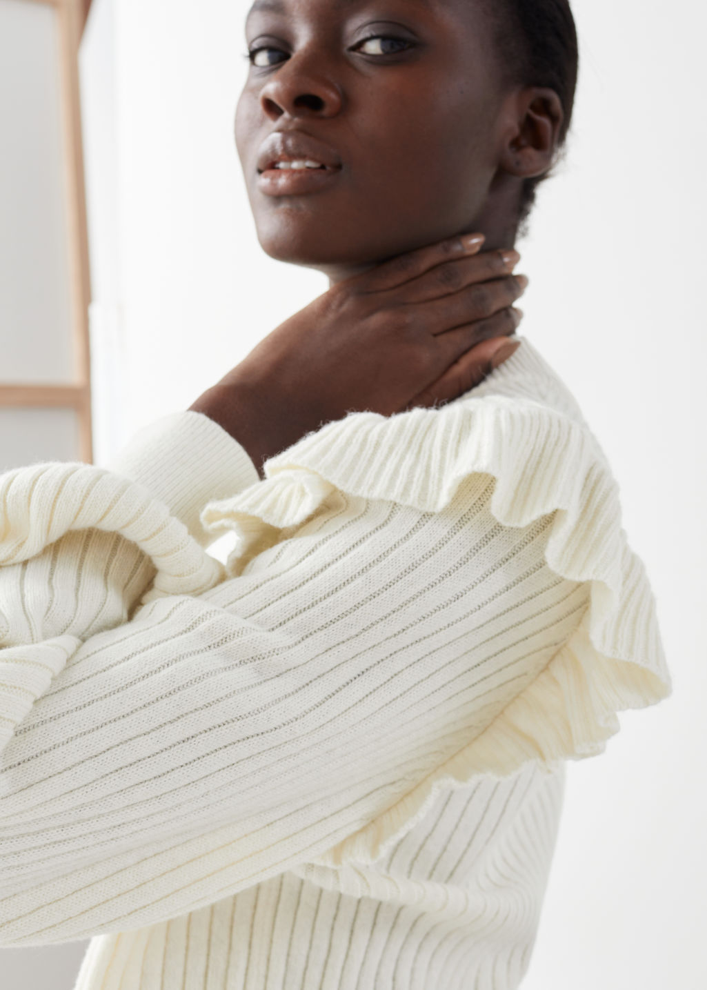 Model side image of Stories frilled mock neck sweater in white