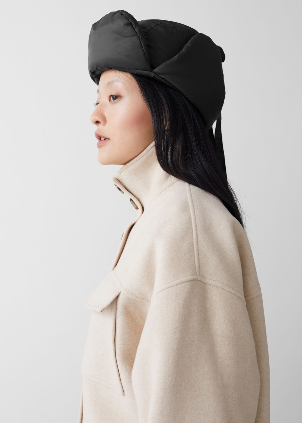 Model side image of Stories padded aviator hat in black