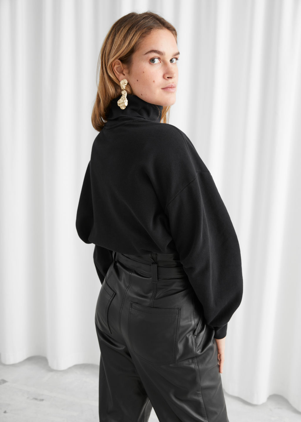 Model back image of Stories organic cotton turtleneck sweater in black