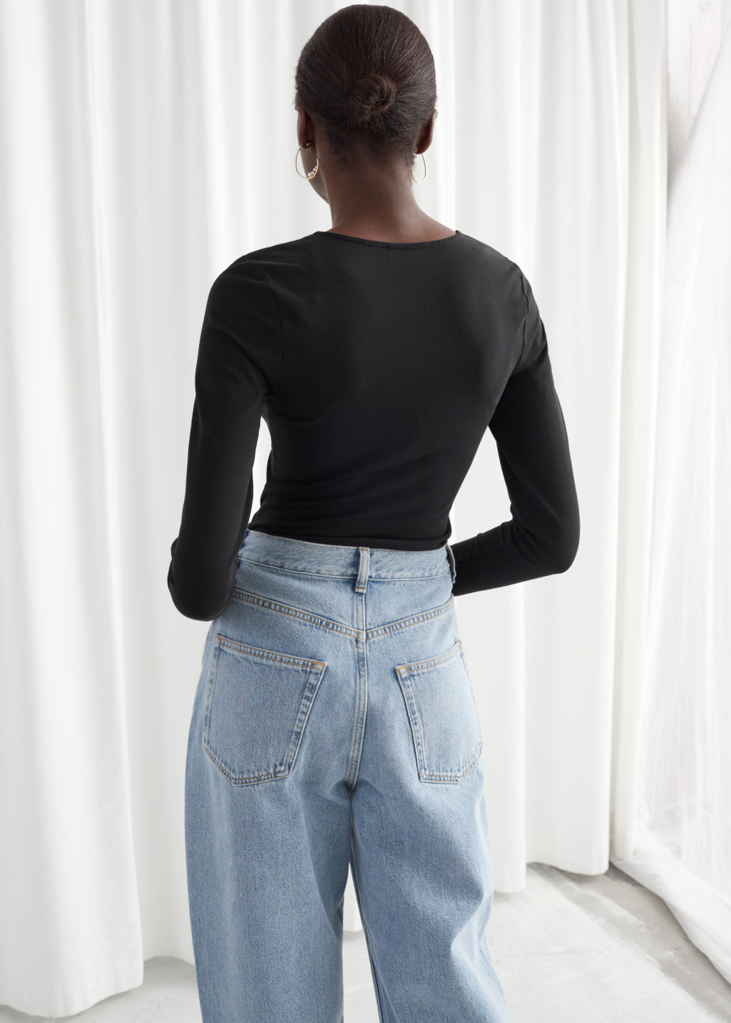 Model back image of Stories organic cotton stretch bodysuit in black