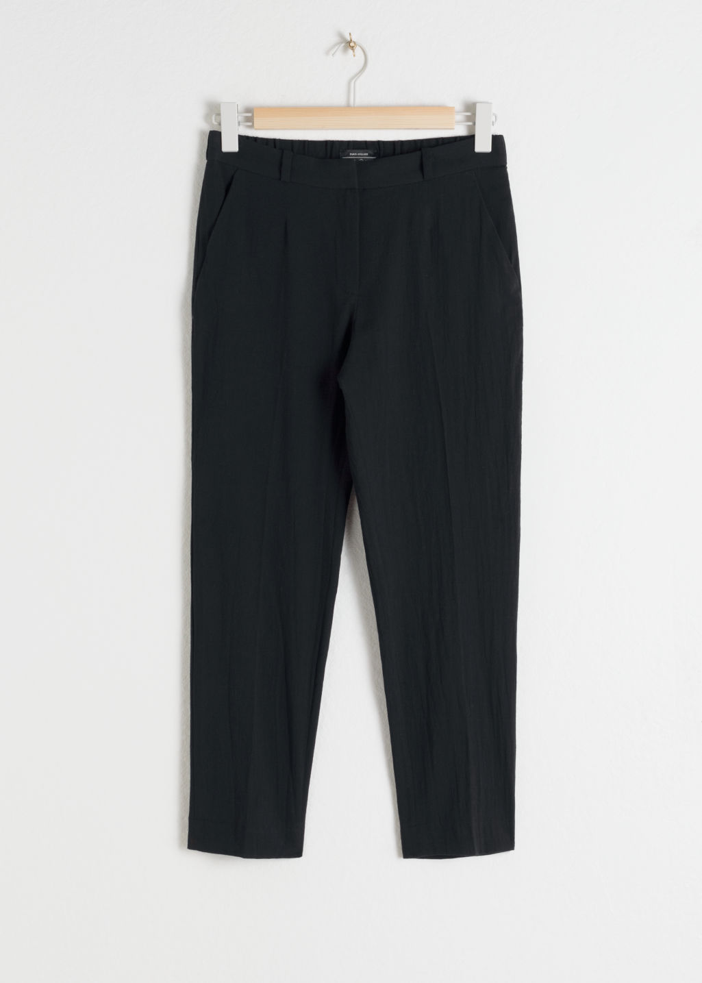 Front image of Stories tapered cotton trousers in black