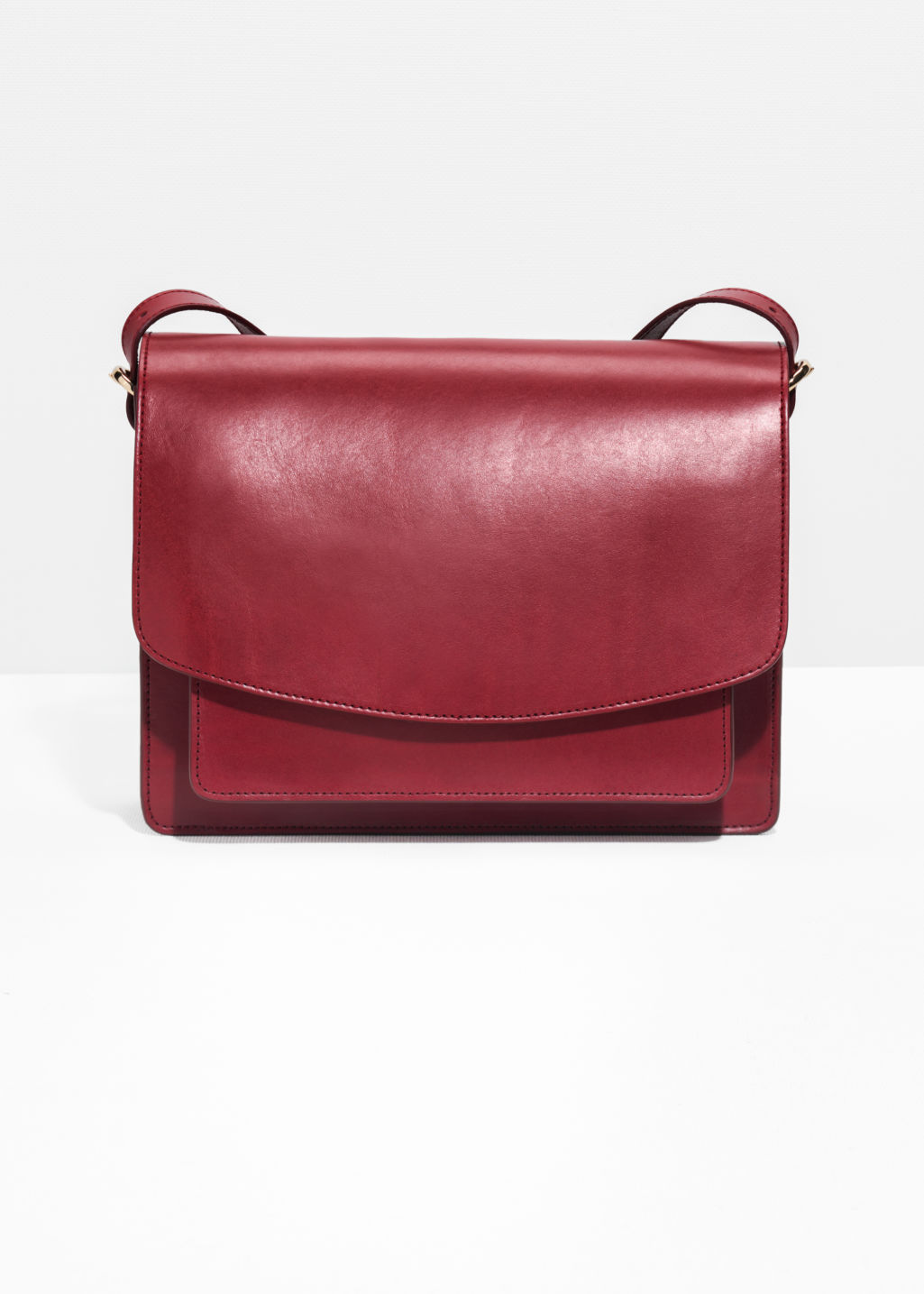 Front image of Stories saddle stitch leather shoulder bag in red