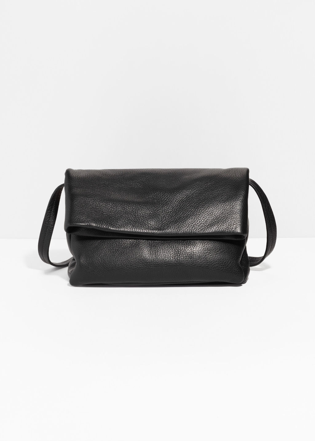 Front image of Stories fold-over suede crossbody bag in black
