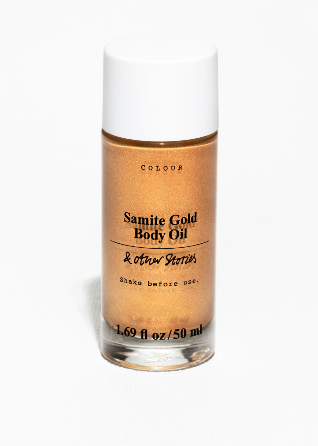 Front image of Stories samite gold shimmer body oil in orange