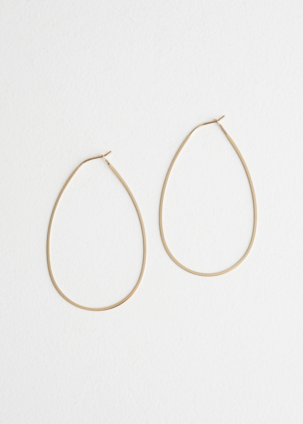 Front image of Stories droplet hoop earrings in gold